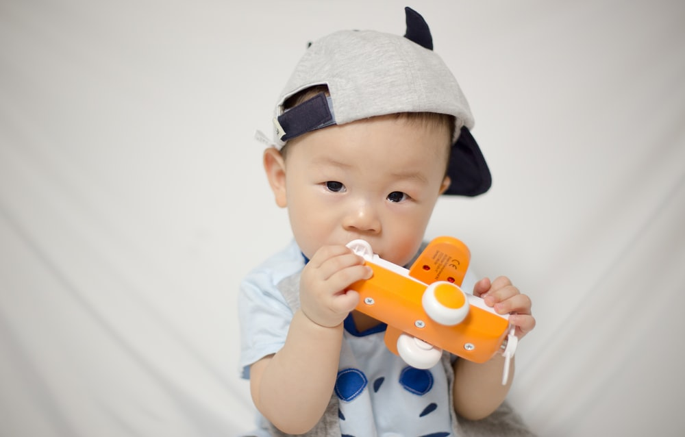 toddler holding white and orange plane toy