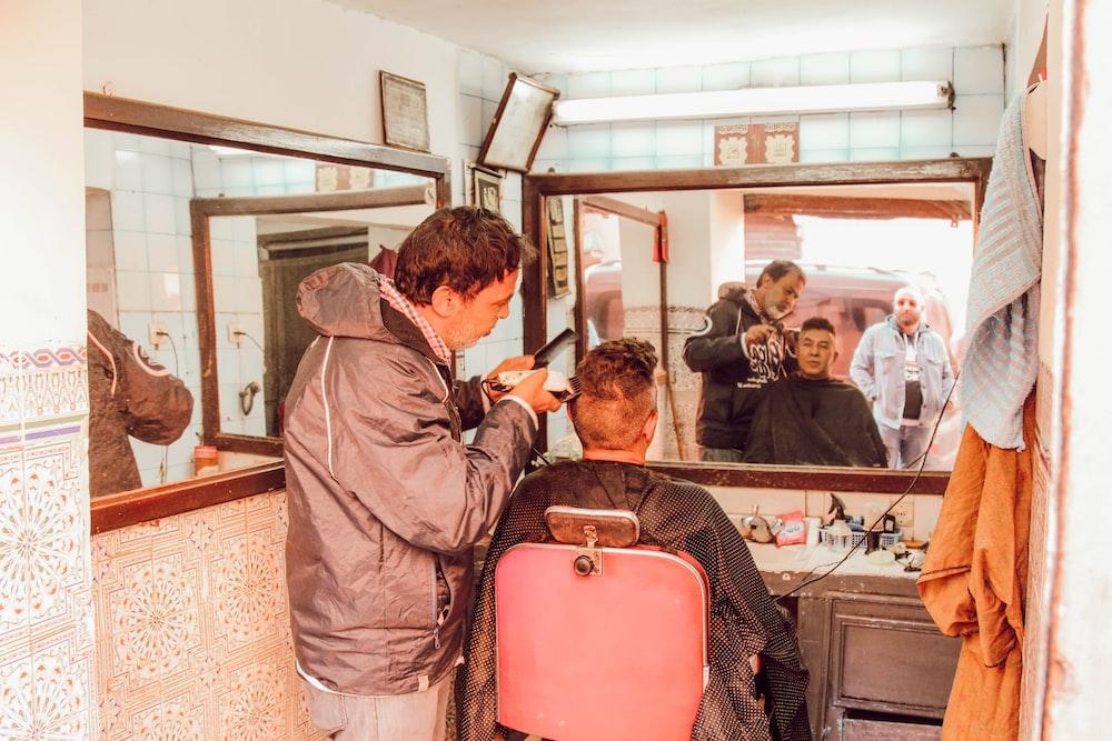 man receiving haircut from man inside shop