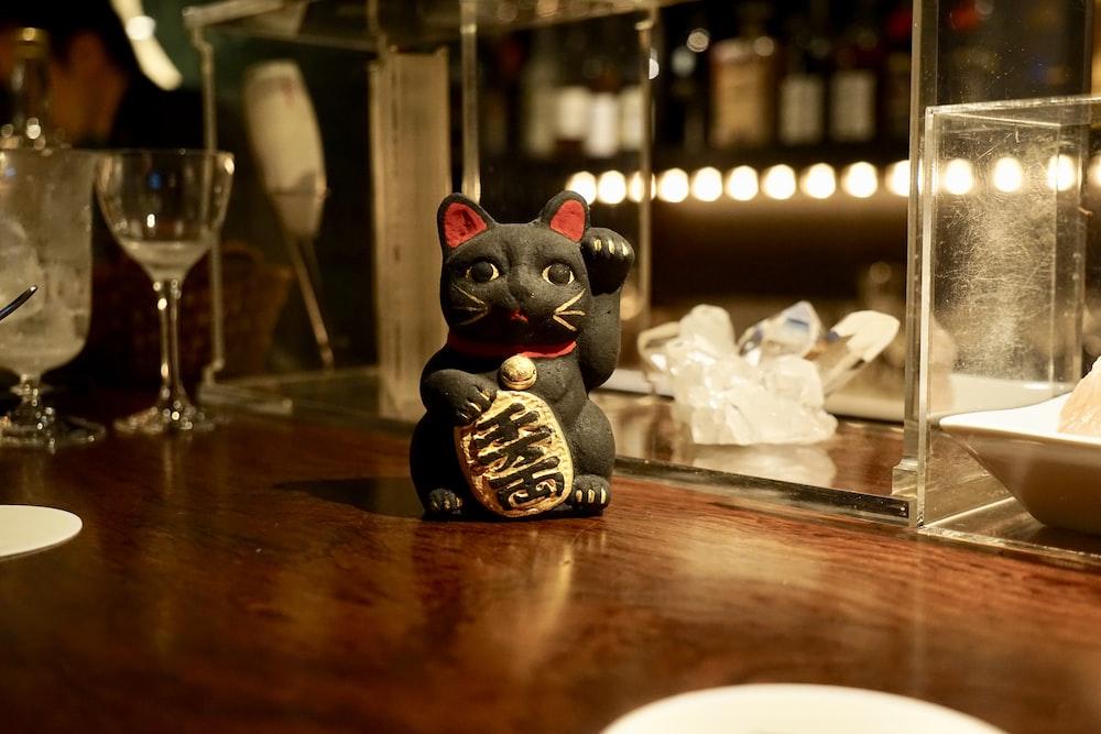 Manikeniko cat figurine on brown wooden surface