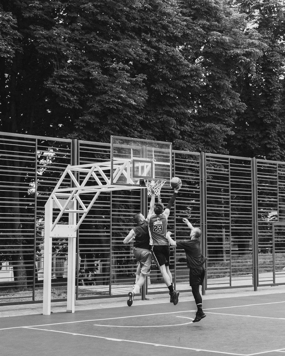 greyscale photography of people playing basketball