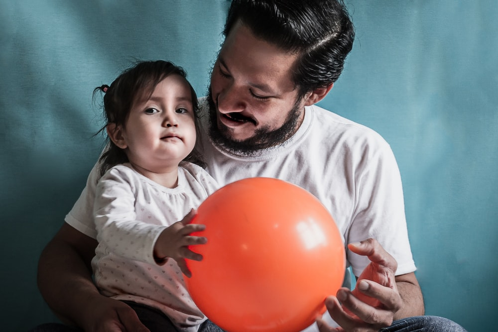 man and baby holding red balloon
