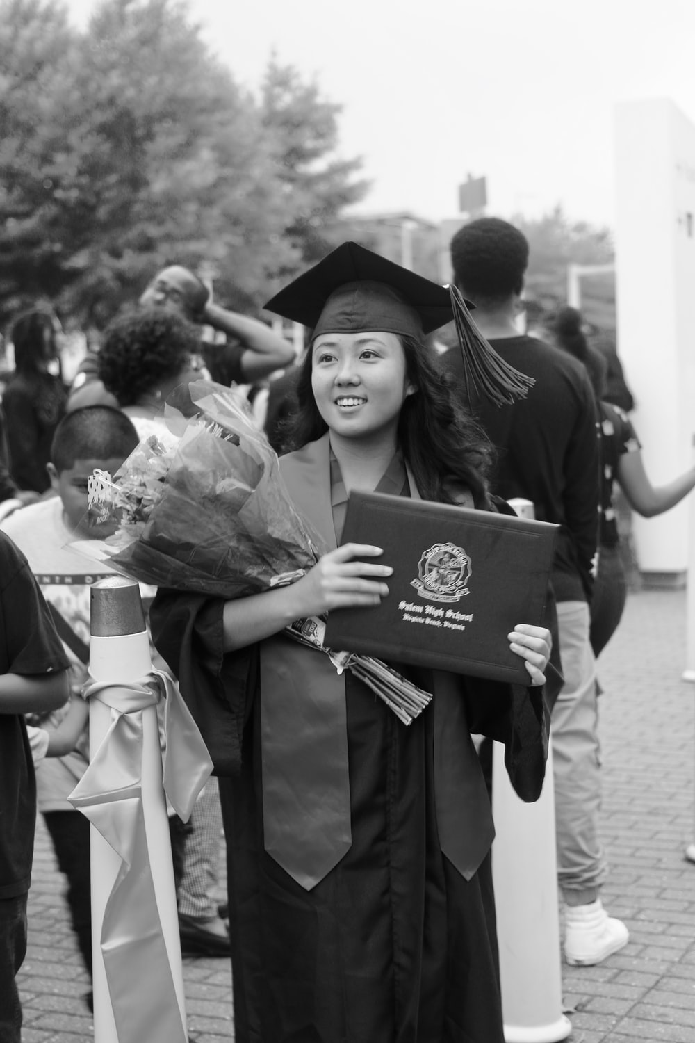grayscale photo of girl wearing graduation gown