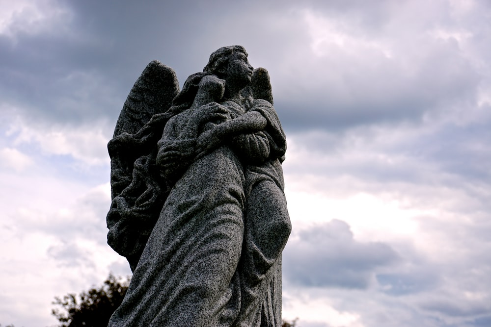 low-angle photography of a male angel hugging woman statue