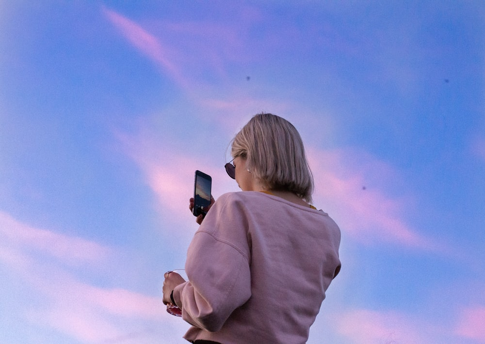 woman in sunglasses and pink top holding phone