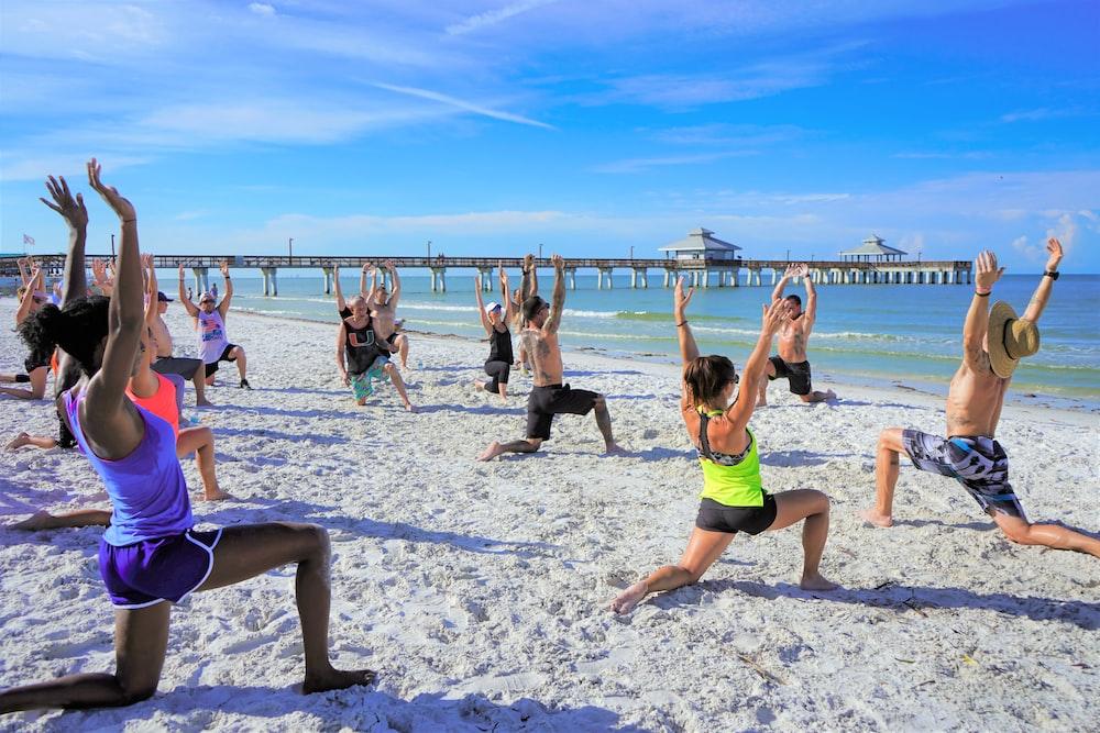 people exercising on seashore during daytime