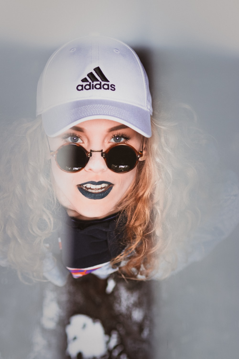 woman in black hoodie with white adidas fitted cap