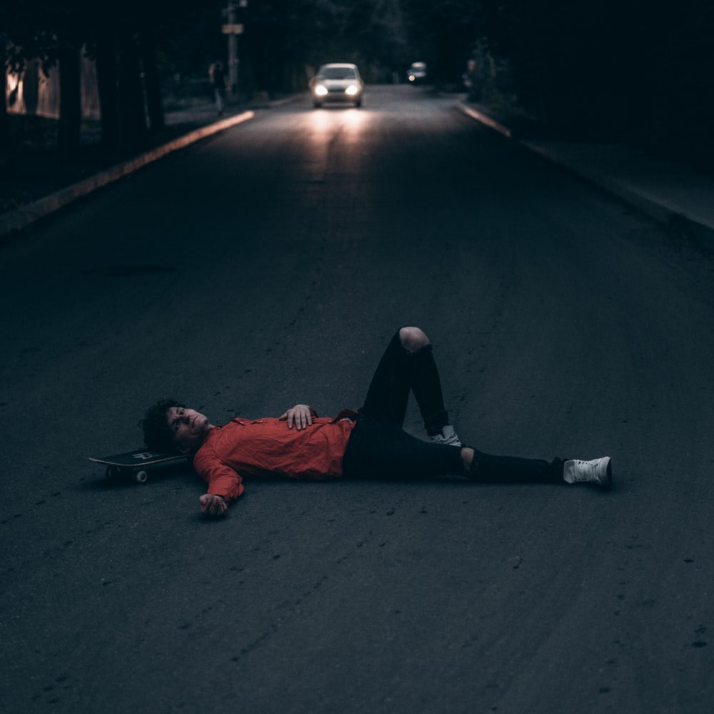 man lying on gray top road during night time