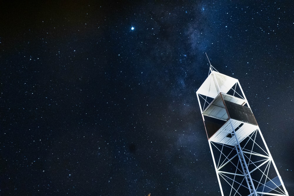 low-angle photography of electrical tower under starry sky during nighttime
