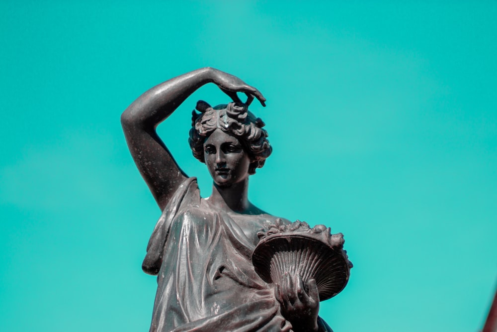 woman lifting hand over head sculpture