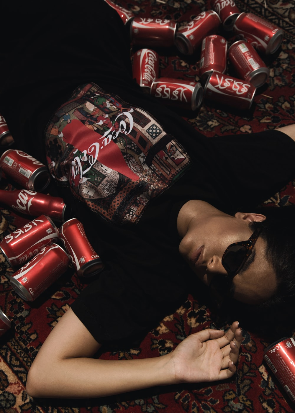 person lying on floor near Coca-Cola cans