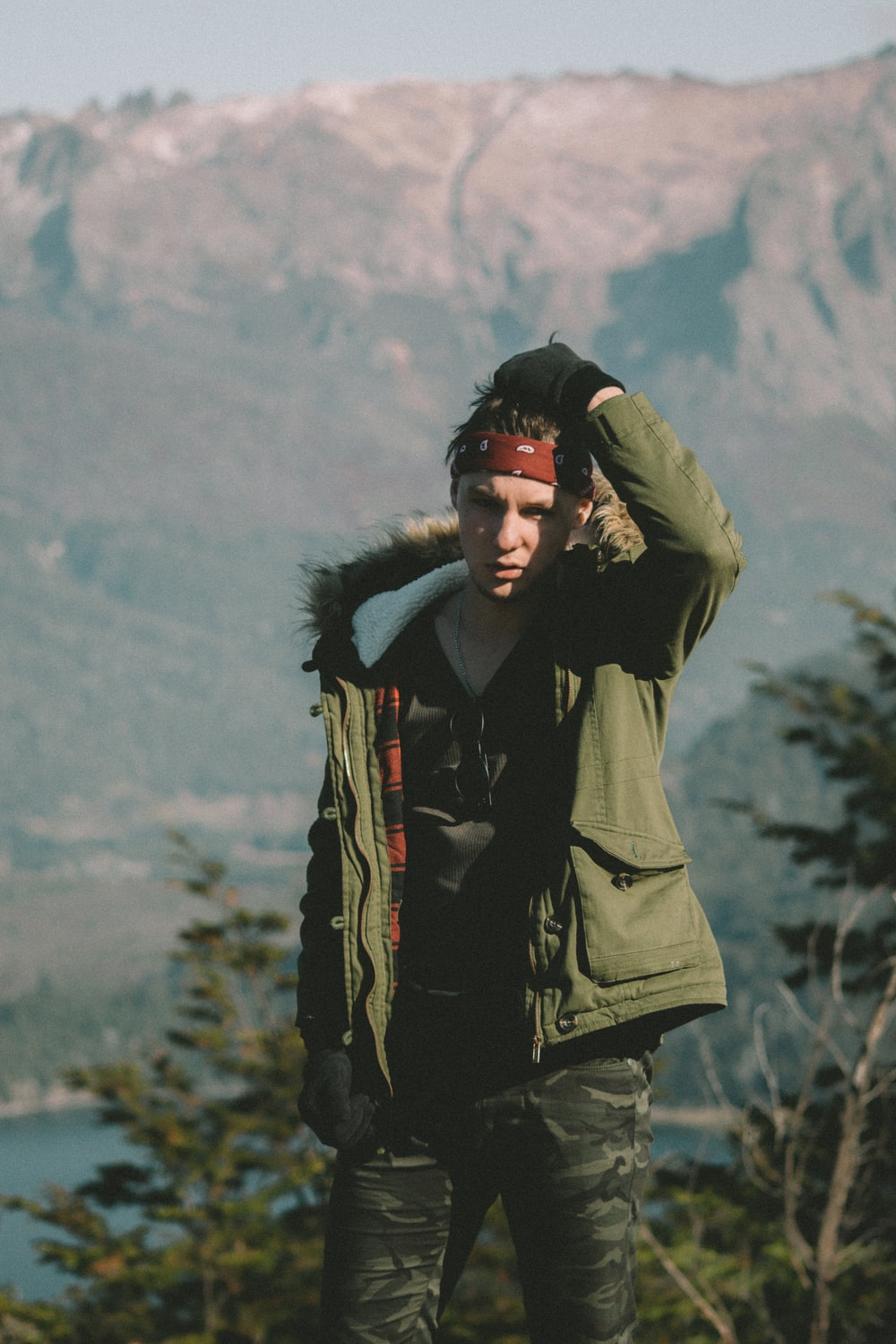 man in green parka jacket standing on hill during daytime