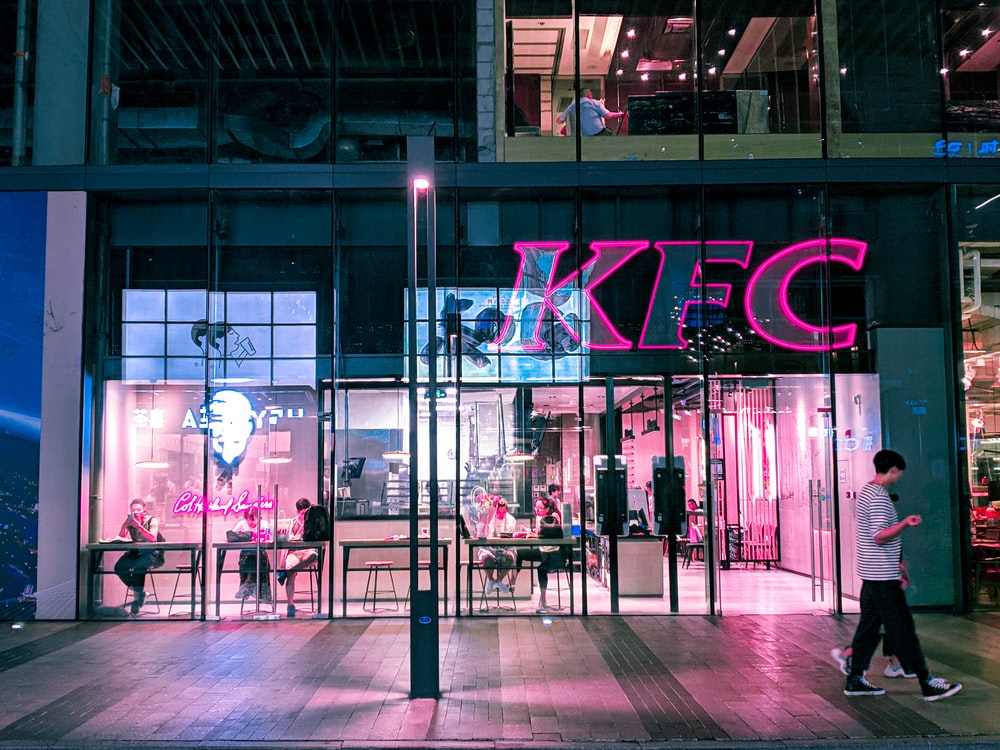 two person walking near KFC building during night time