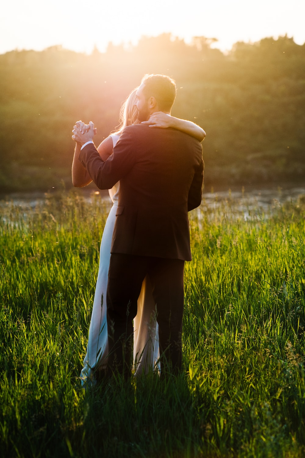 man and woman dancing on green grass field
