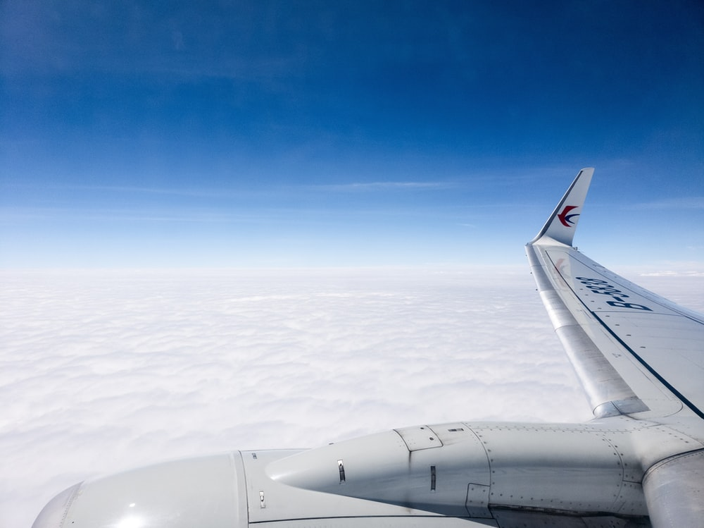 aerial photo of plane flying above clouds under clear blue sky
