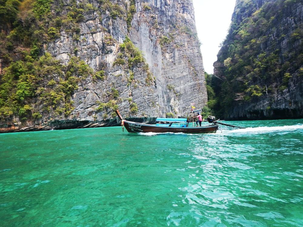 man riding on boat near cliff