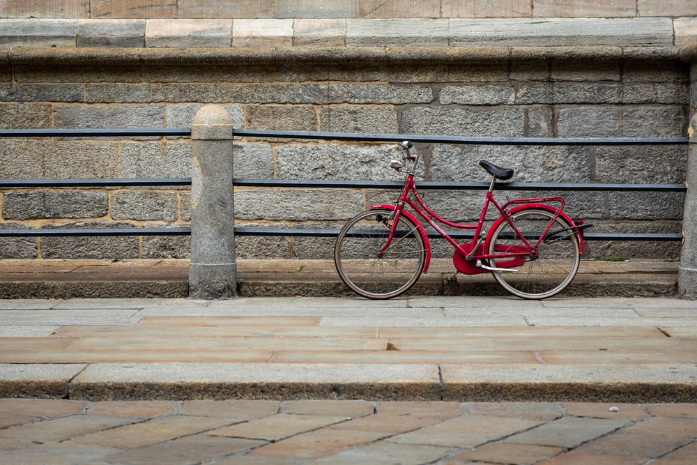 red bicycle leaning on rail