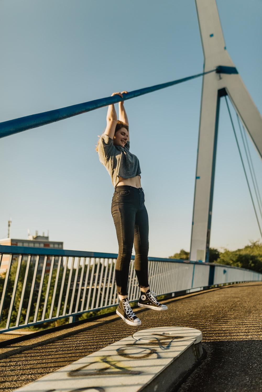 woman hanged on metal bar in the bridge
