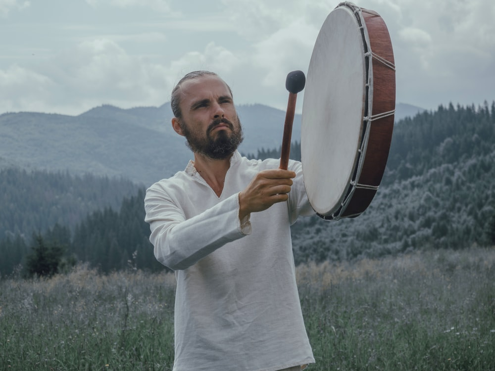 man playing percussion instrument on grass field near forest, journey into shamanism, shamanic healer