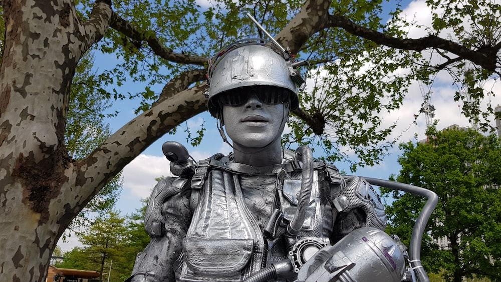 man in hat statue under tree