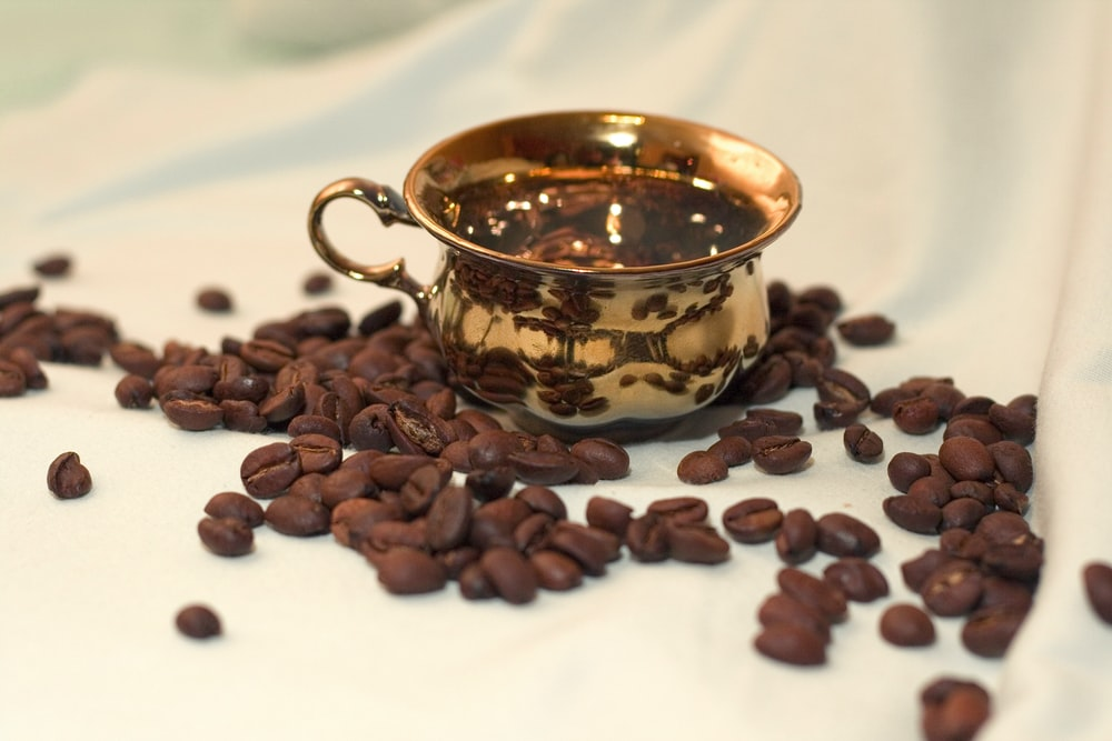 brass-colored teacup with coffee beans