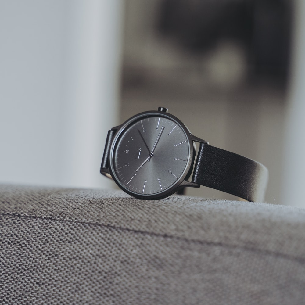 selective focus photography of black analog watch with black strap