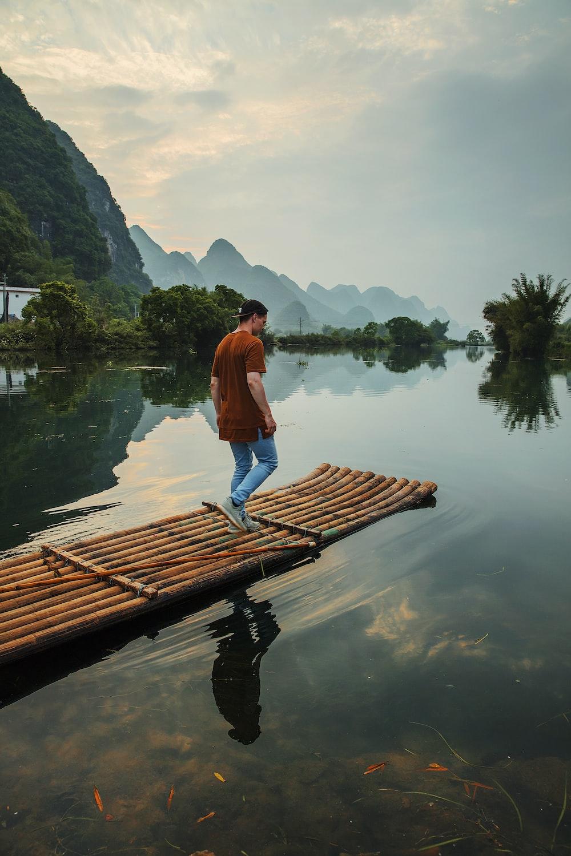 man walking on bamboo dock during daytime