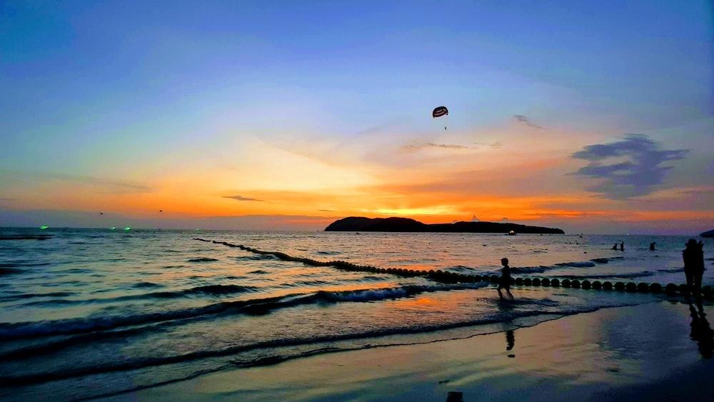 people in beach under orange sky at sunset