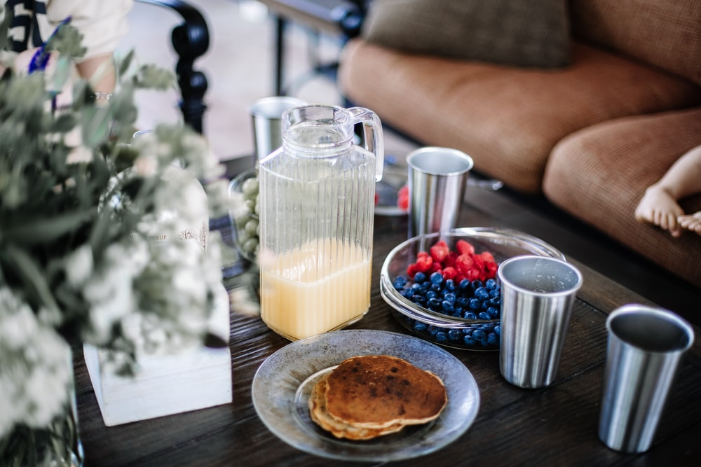 four gray cups beside bowls with berries and pitcher with half-empty juice near pancakes on table