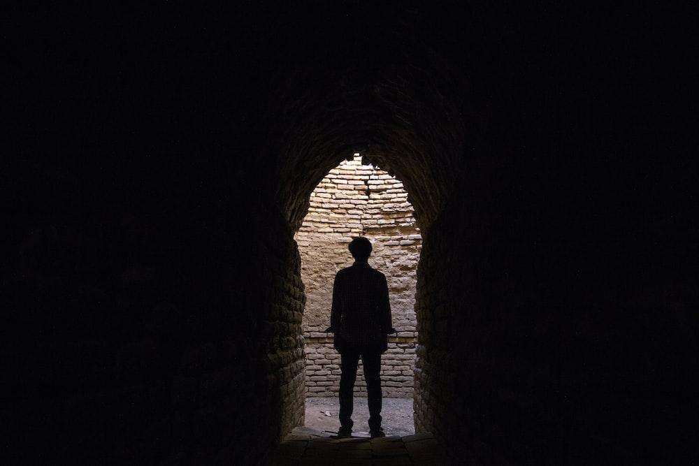 silhouette of man under arch hallway
