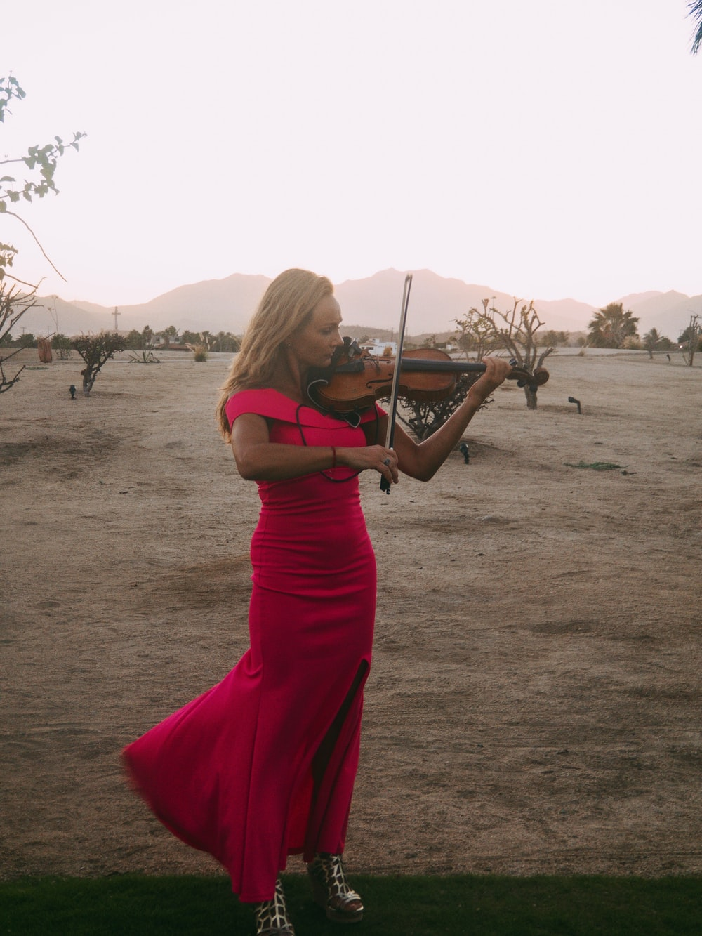 woman standing and playing violin on brown field