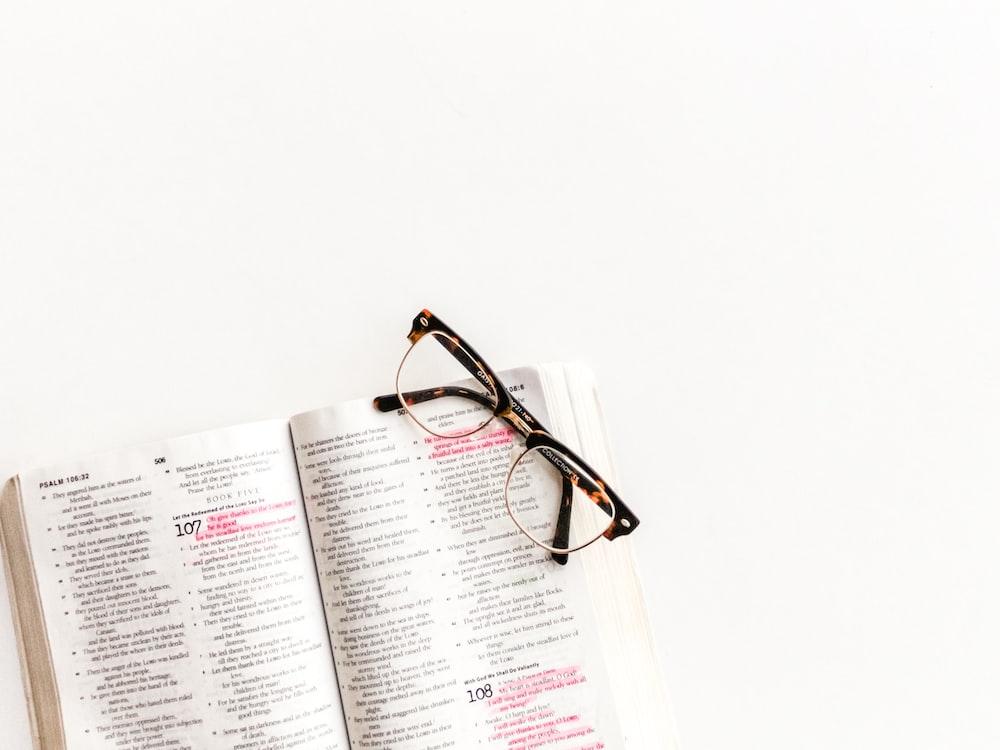 Clubasmter-style eyeglasses on open book