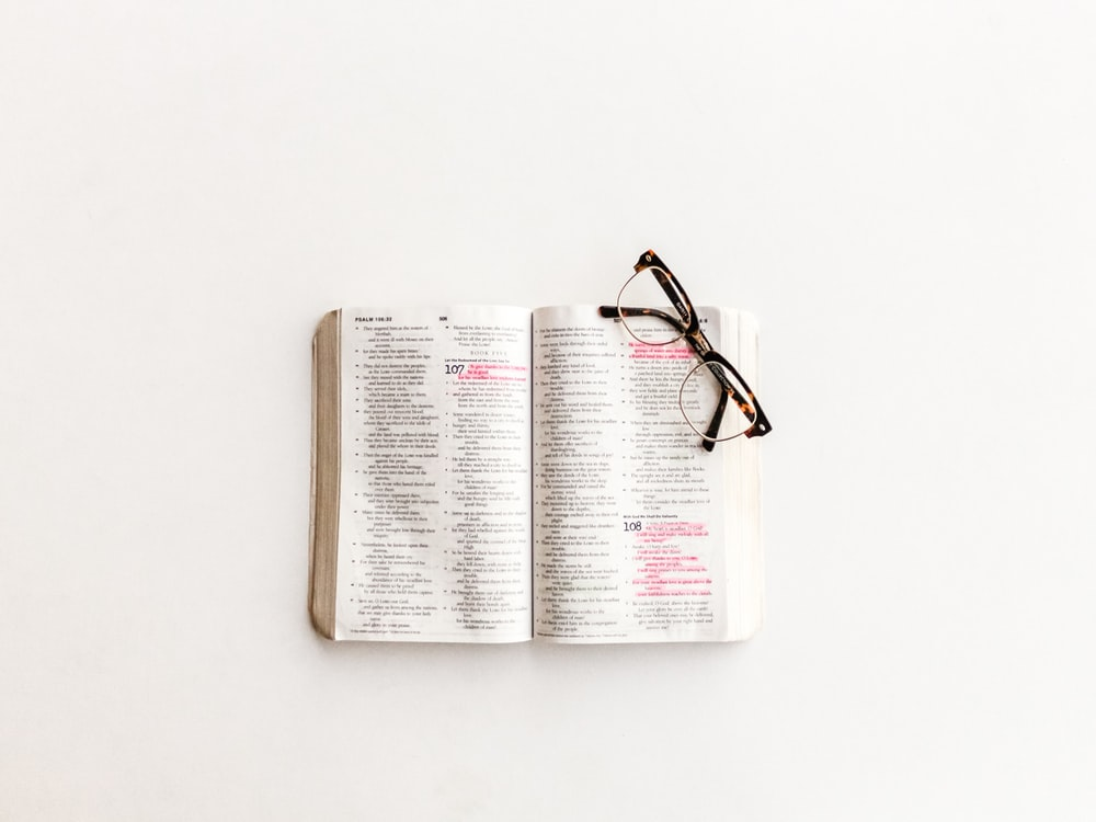 white book page and eyeglasses