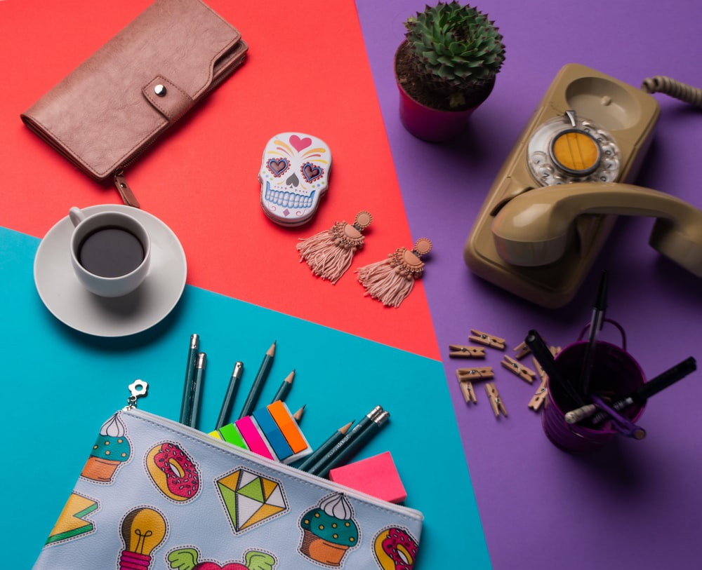 pencils on pouch beside coffee cup with saucer, cup with ballpoin pens near brown telephone, succulent plants, kalavera case, and brown wallet