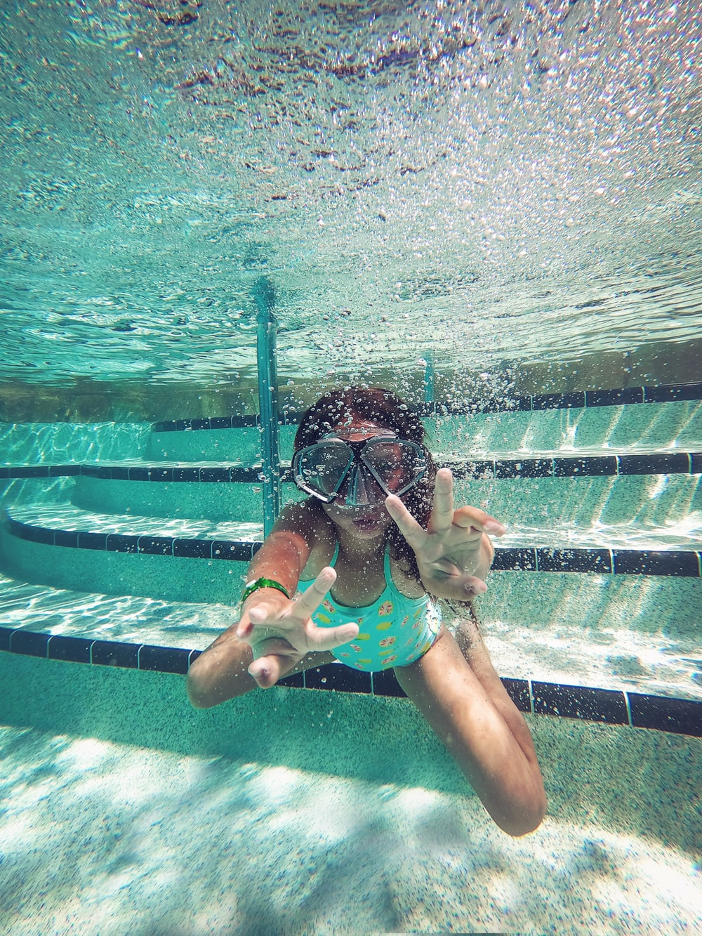 person swimming under water during daytime