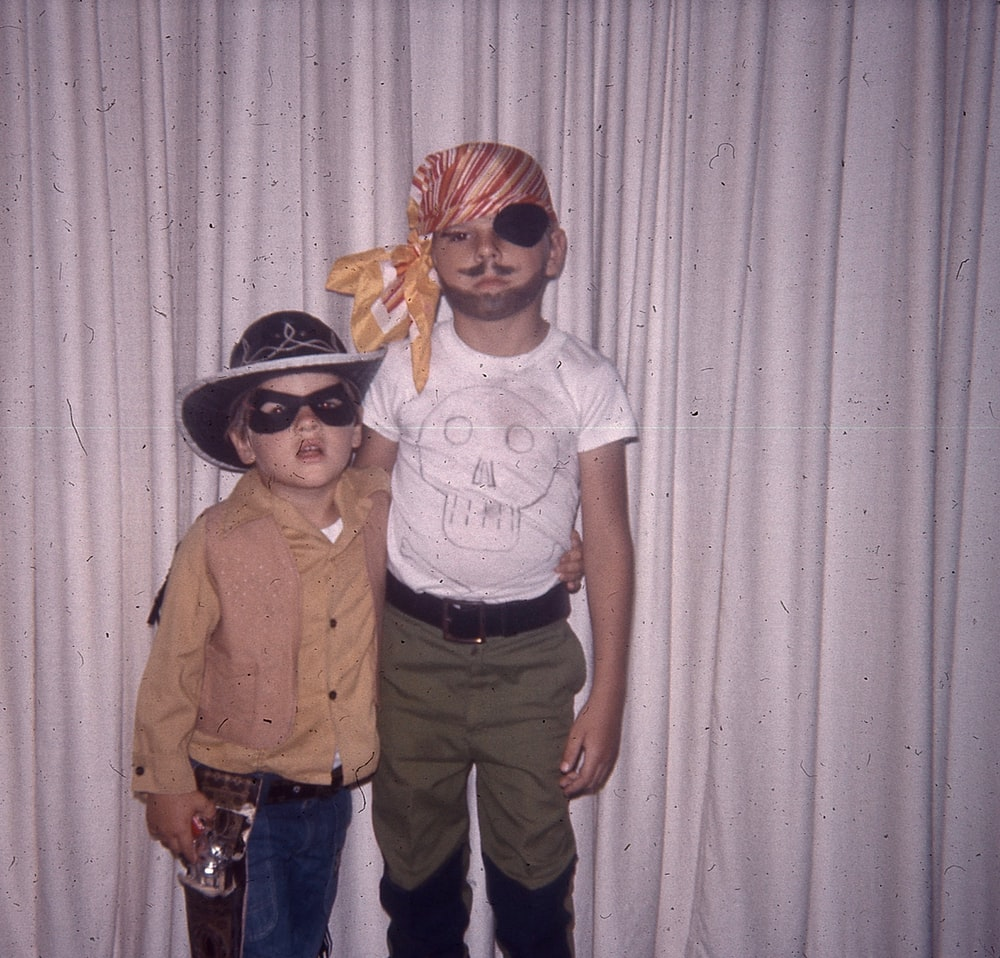 two boys wearing pirate and cowboy costumes