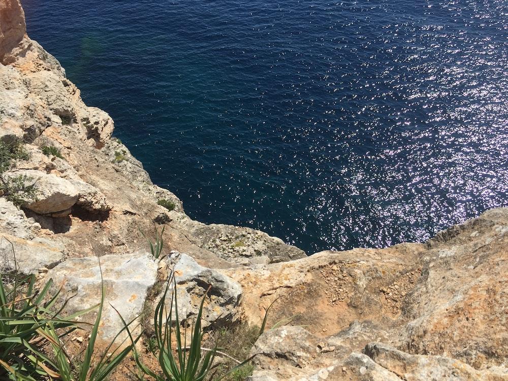 brown rocks across body of water