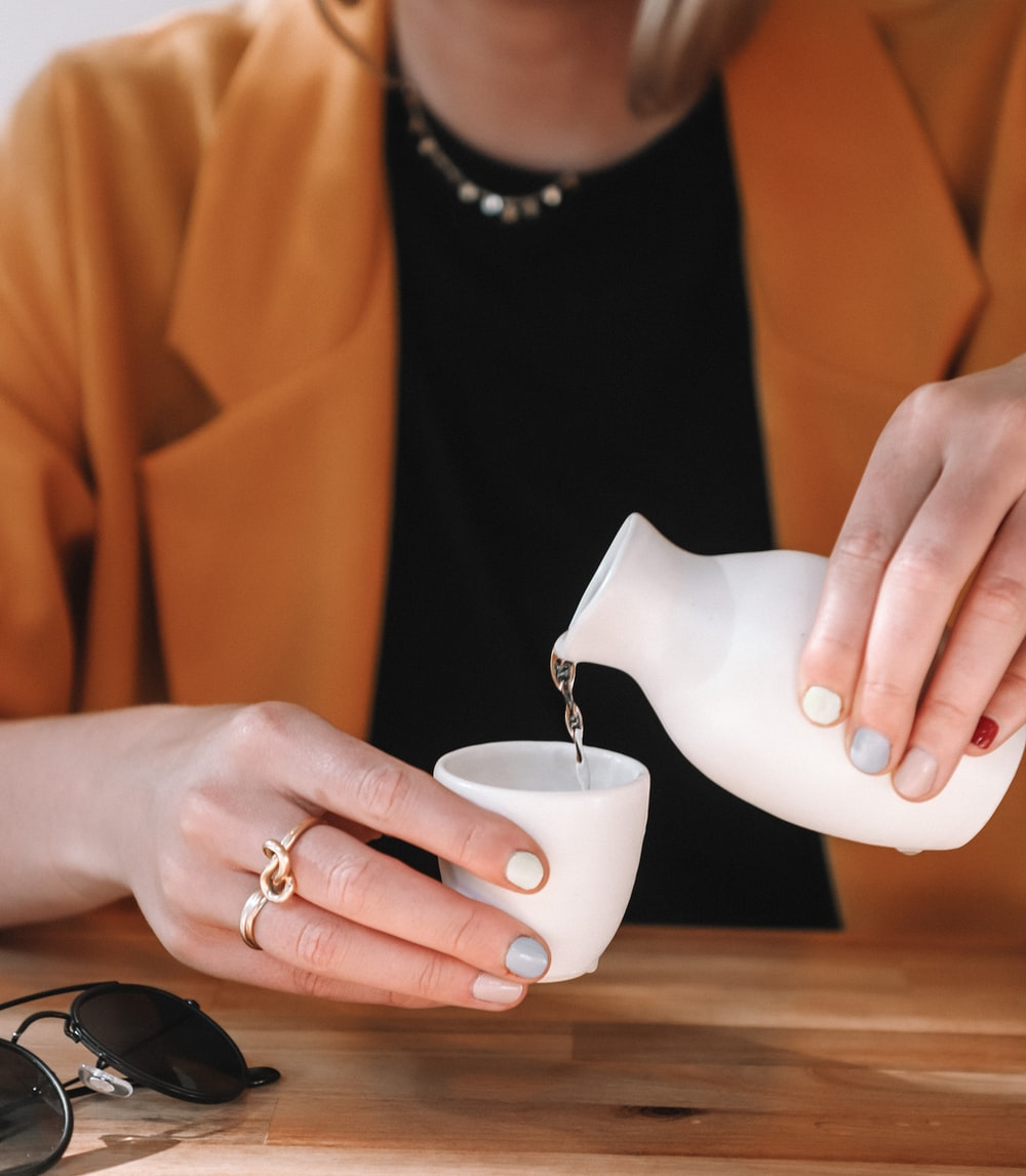 woman pouring water on ceramic shot glass