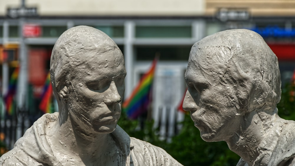 two human sculptures near building