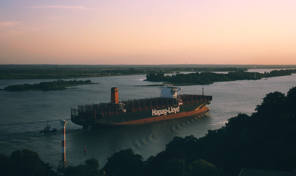 black and orange cargo ship sailing