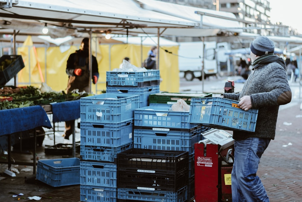 man carrying blue crates