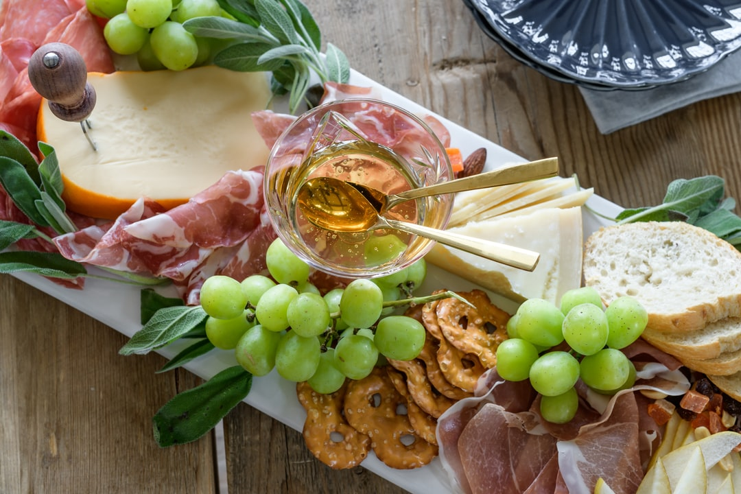 Charcuterie board filled with fine cheeses, grapes, honey, pretzels and baguette bread