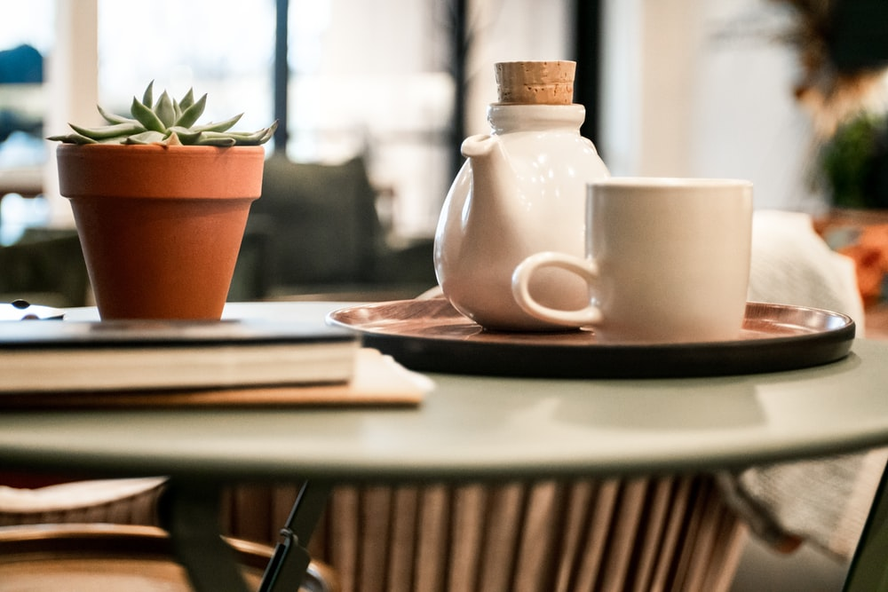 white cup beside teapot on tray