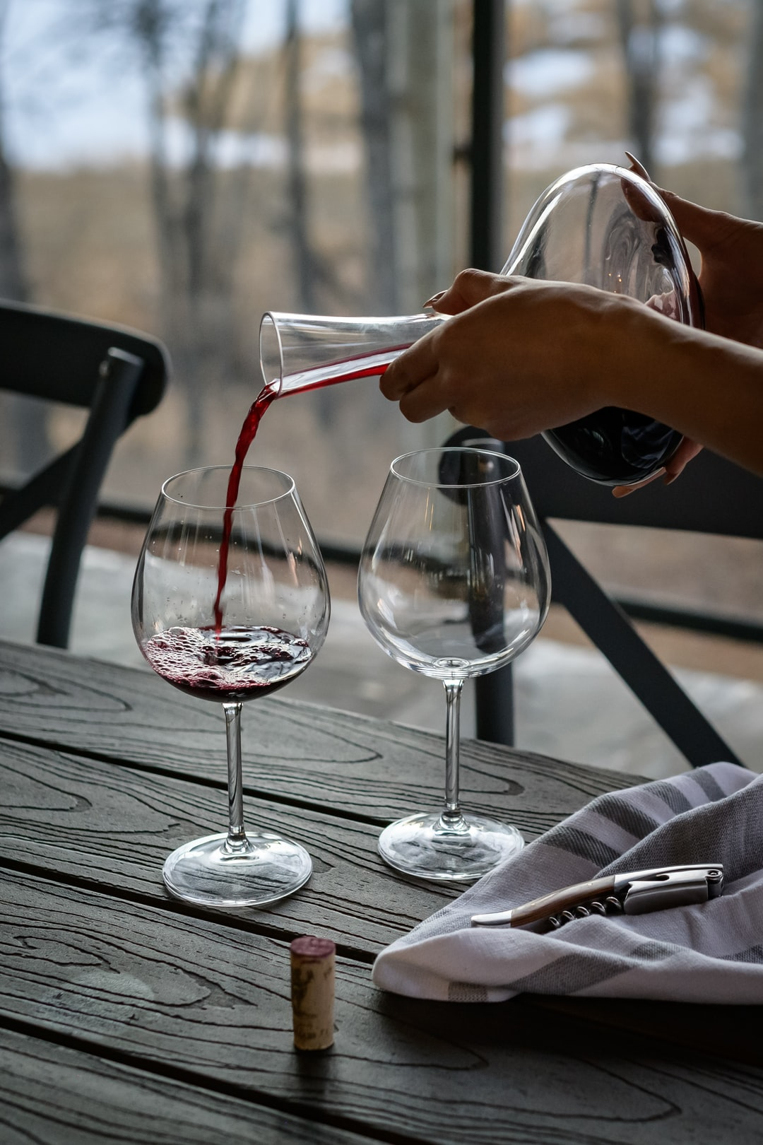 Pouring wine into glass from a carafe in an outdoor fine dining setting