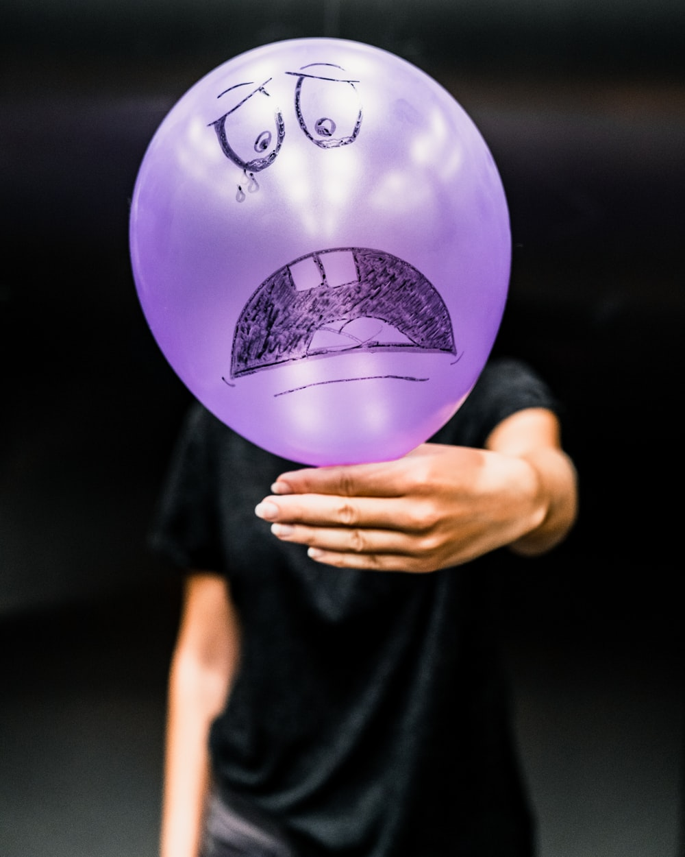 man in black t-shirt and purple balloon