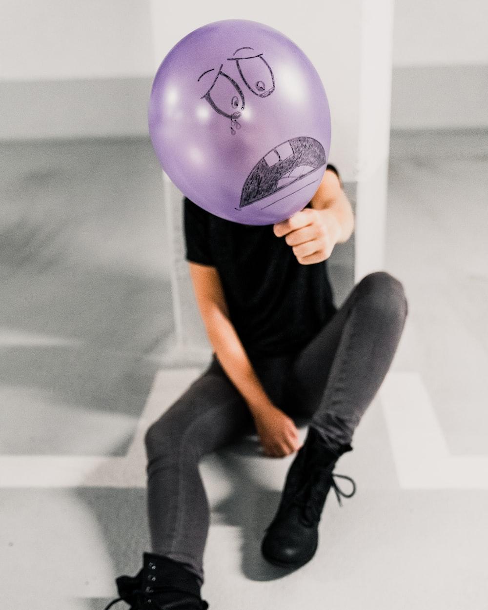 sitting man holding sad balloon