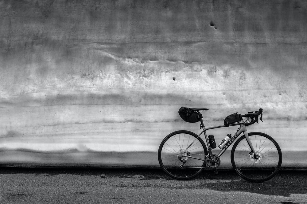 gray bicycle parked beside wall