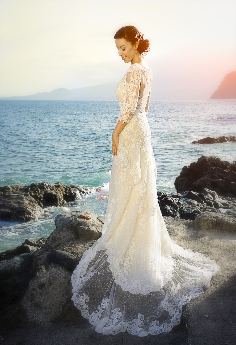 woman wearing white gown standing on rocks across body of water
