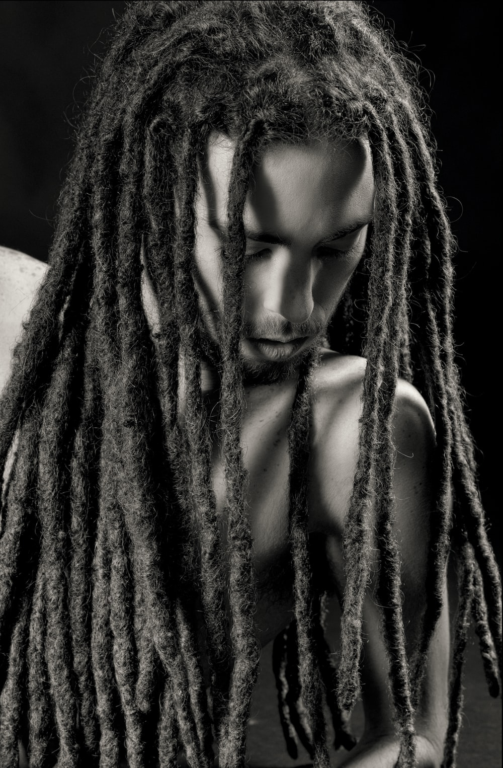 gray scale photo of man with dreadlock hairstyle