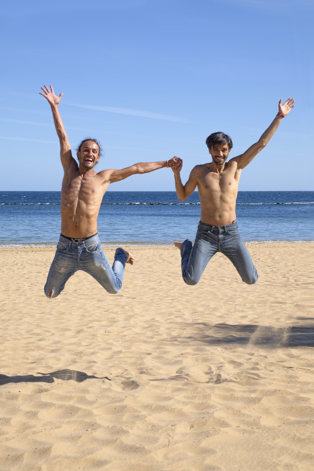 two man jumping above brown beach sand