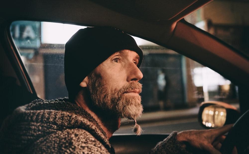 man wearing black knit cap riding vehicle during daytime